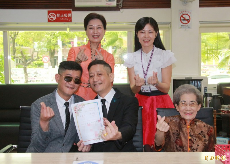 男性伴侶王富生(中)與沈其祥(左下)在王媽媽(右下)與王姐姐(左上)陪同見證下完成結婚登記。(記者陳冠備攝)