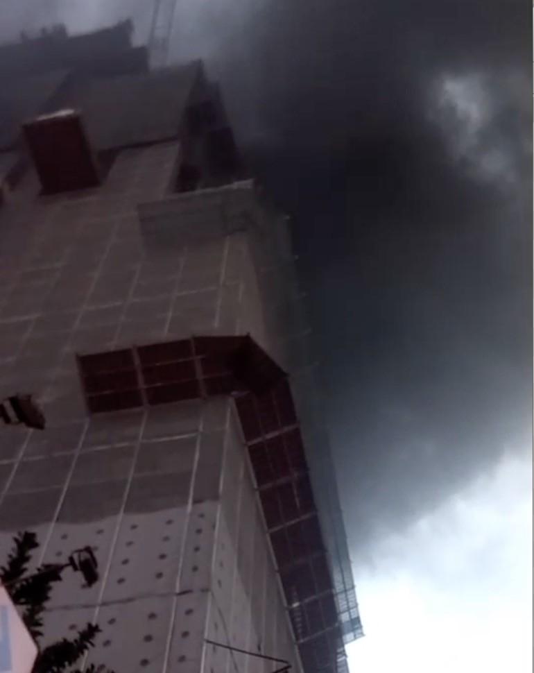 今天下午6點左右,中和區景新街355巷一處工地地下室起火,黑煙竄天。(記者陳薏云翻攝)