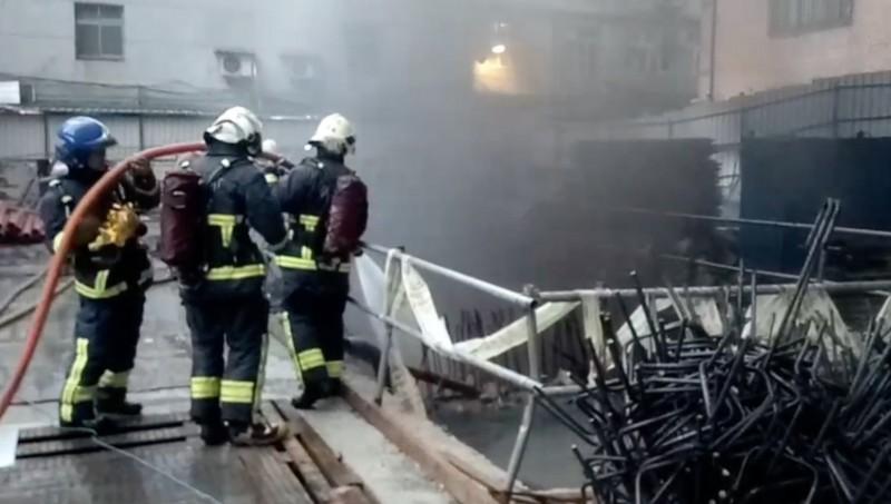 今天下午6點左右,中和區景新街355巷一處工地地下室起火,黑煙竄天,警消趕赴現搶救。(記者陳薏云翻攝)