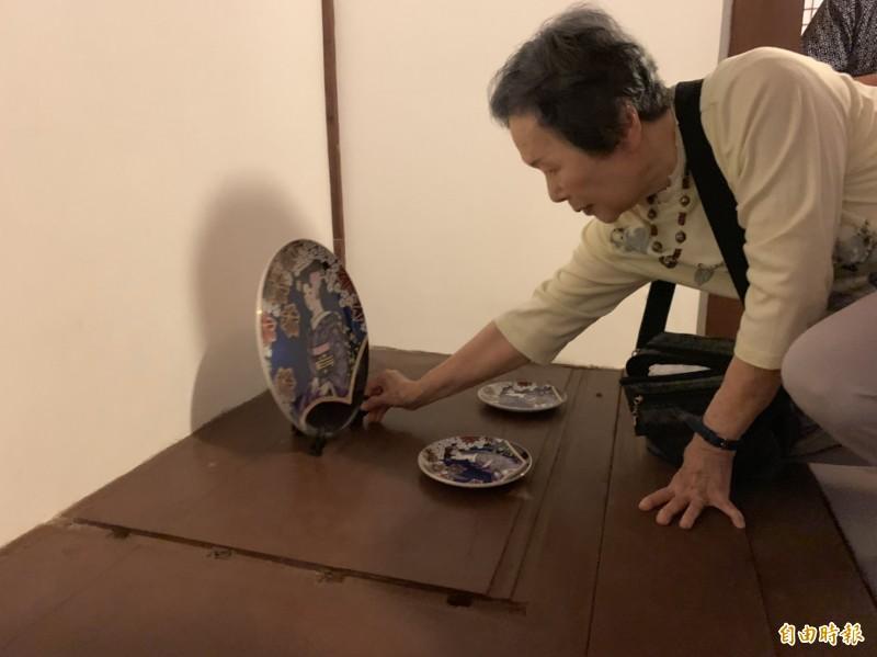 今泉光子回憶兒時,將自日本帶來的瓷器擺回記憶中原處。(記者王峻祺攝)