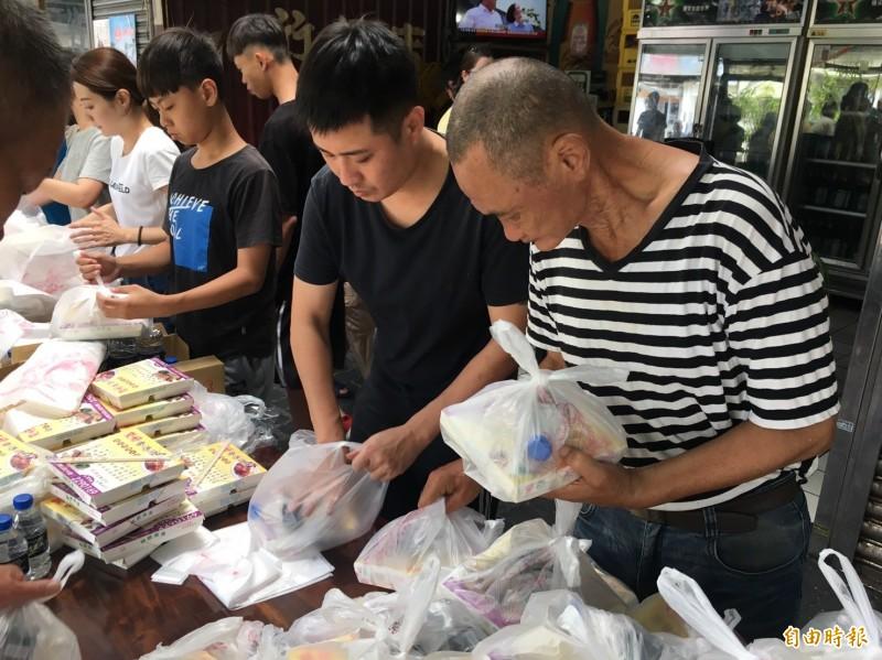 歐光榮(右1)4年來每個星期六都發出300個便當給街友。(記者王捷攝)