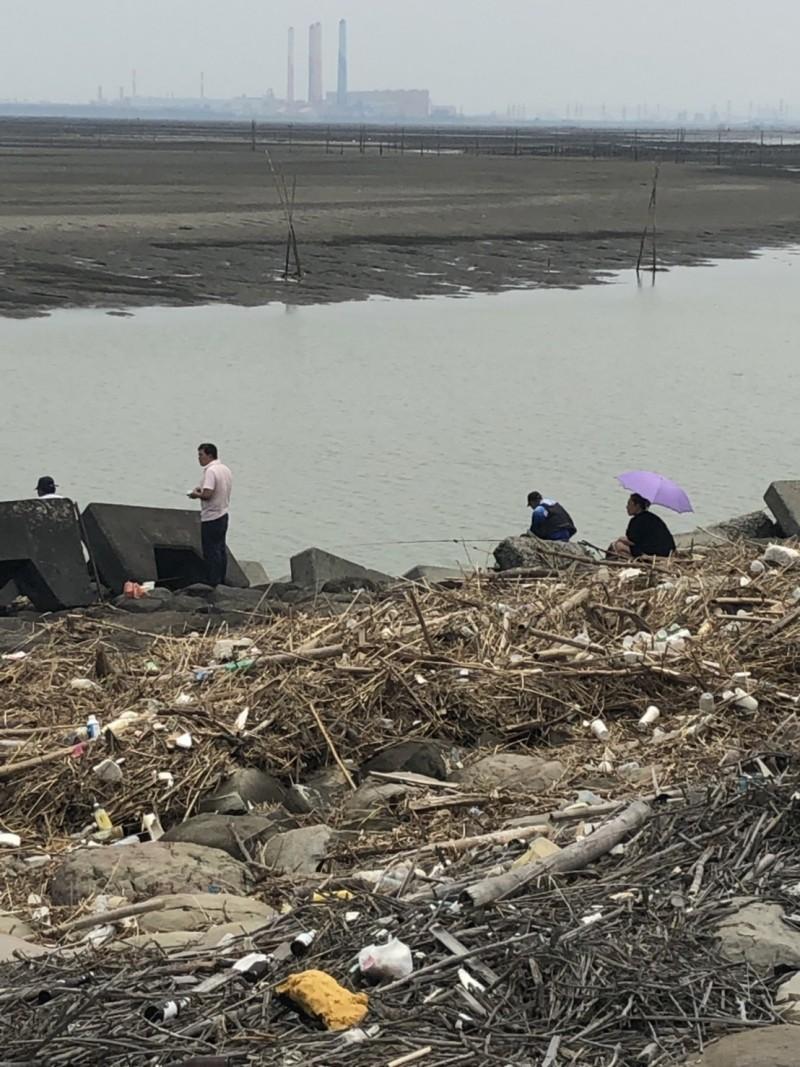 釣客踩過垃圾山蹲在垃圾堆裡釣魚,民眾嘲諷此景成世界奇景,「伸港獨有」!(記者張聰秋翻攝)