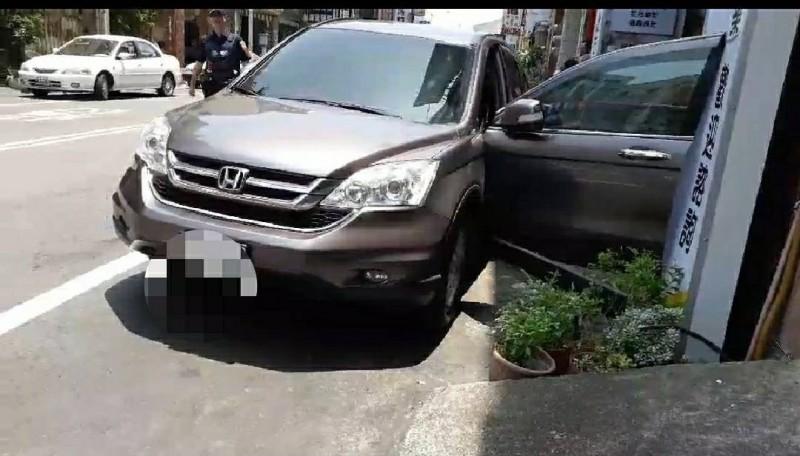 婦人油門誤當煞車踩,結果倒退撞後車,門卡花圃動彈不得。(記者蔡政珉翻攝)