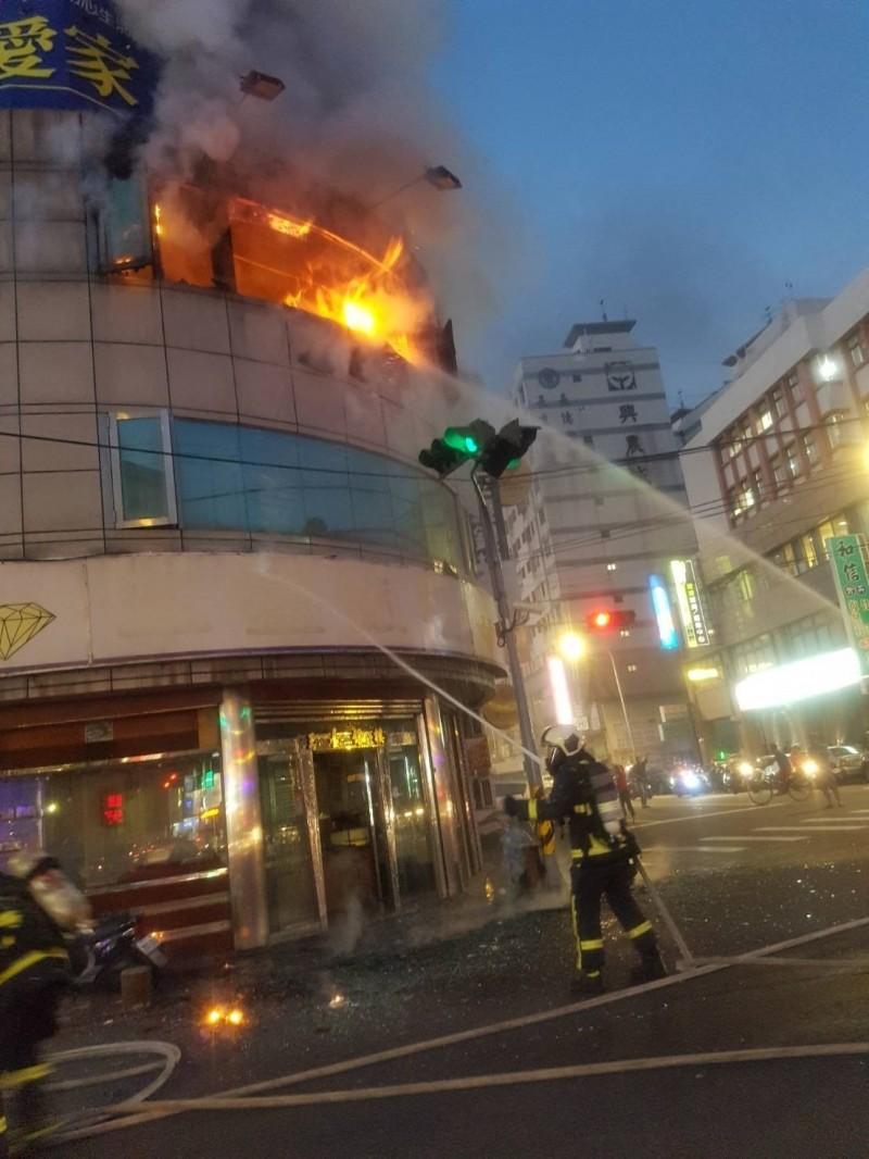 大里中興路2段和德芳路1段口的一家銀樓今晚起火燃燒,消防人員獲報到場搶救。(記者陳建志翻攝)