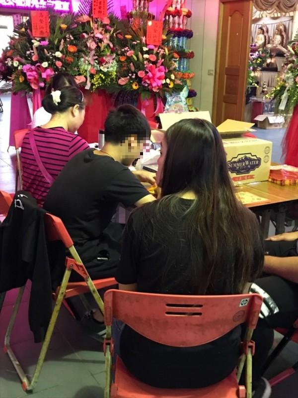 張生今天下午泰半時候跟著親友靜靜坐在父親靈前折蓮花或是元寶,不發一語。(記者黃美珠攝)