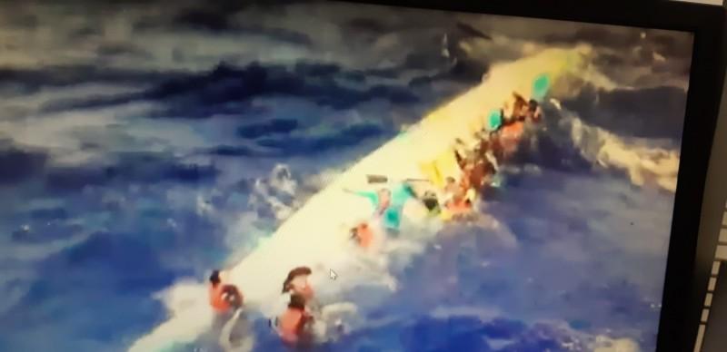 船員抱著翻覆的龍舟載浮載沉。(記者黃明堂翻攝)