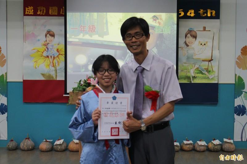 成功國小校長朱劍忠,頒發畢業生吳佳穎畢業證書。(記者劉禹慶攝)