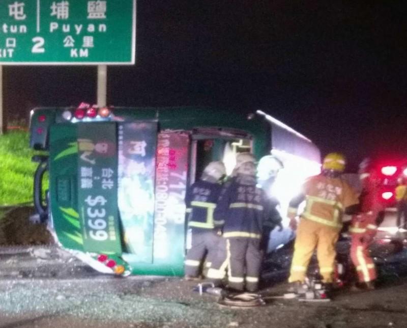 國道1號彰化戰備道今晚驚傳重大車禍,1輛阿羅哈遊覽車衝出邊坡直墜平面道路,10多人受困,消防員破壞車體搶救。(記者湯世名翻攝)