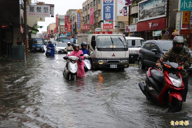 永康大灣路一帶積淹水,騎士只好牽車經過。(記者萬于甄攝)