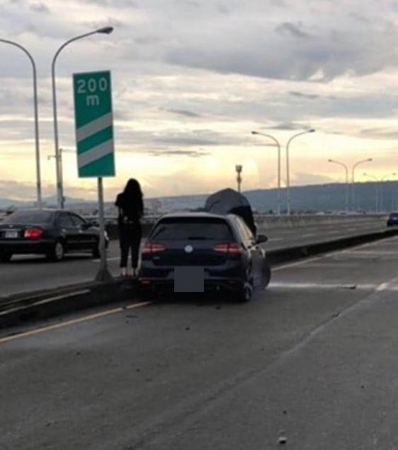 邱姓女駕駛肇事後僅輕微擦傷,站在車頭嚴重毀損的車子旁。(記者陳建志翻攝臉書《爆料公社》)