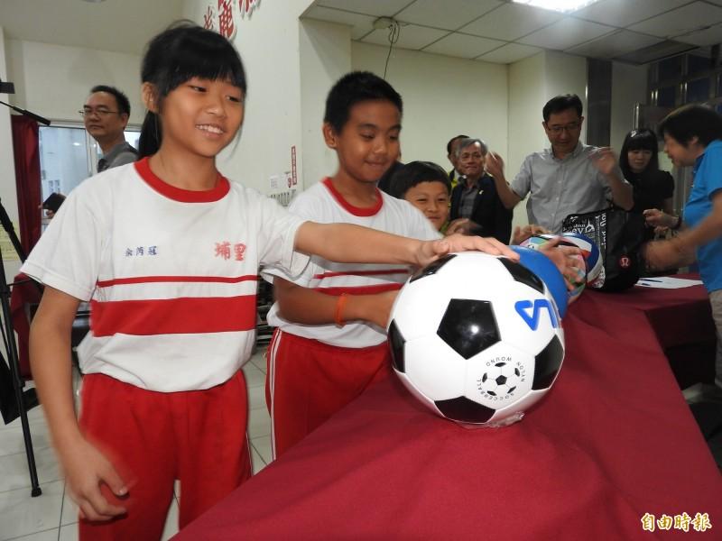 小朋友看到全新、色彩繽紛的足球、排球及籃球,開心得愛不釋手。(記者佟振國攝)