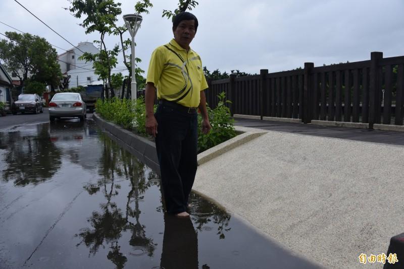 屏東市代李進是指大堀道路沒有排水溝造成積水嚴重。(記者葉永騫攝)