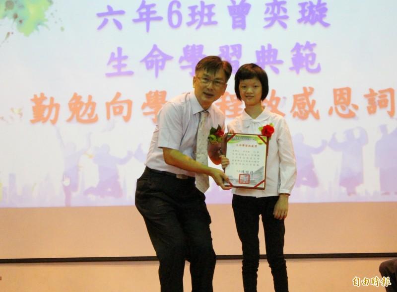 草屯鎮炎峰國小校長陳恒聰(左),頒發生命學習典範獎給曾奕璇(右)。(炎峰國小提供)