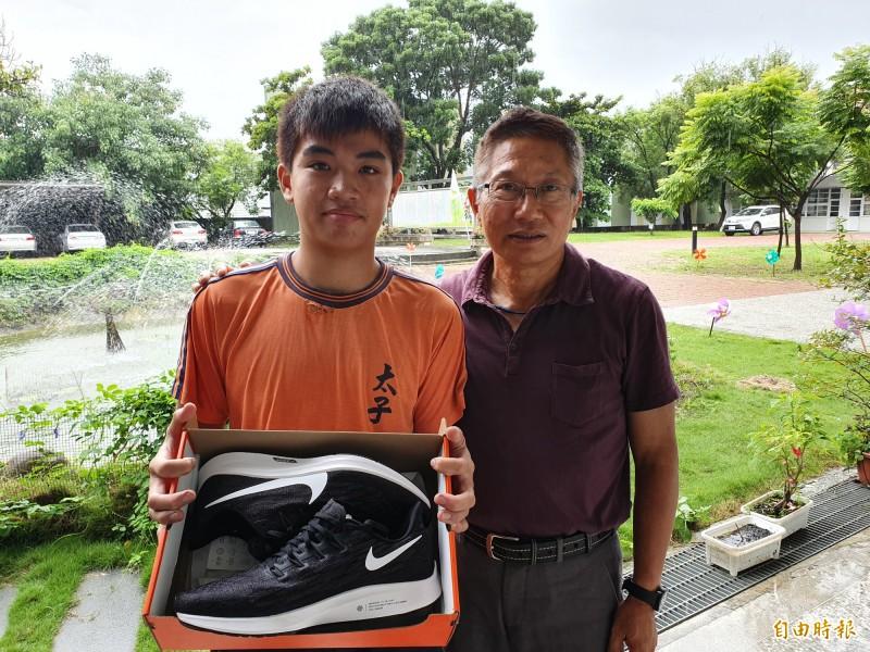 太子國中國三的黃建勝(左)今年除獲得南市技藝競賽機車修護第1名,也獲得全國技藝競賽績優,是全南市8位績優其中之一。校長王沐錱(右)贈球鞋表揚鼓勵。(記者王涵平攝)
