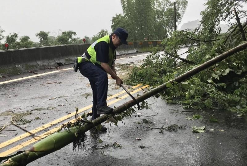 員警向農友借來砍刀,準備將傾倒的檳榔樹砍斷,以便移到路旁。(記者歐素美翻攝)