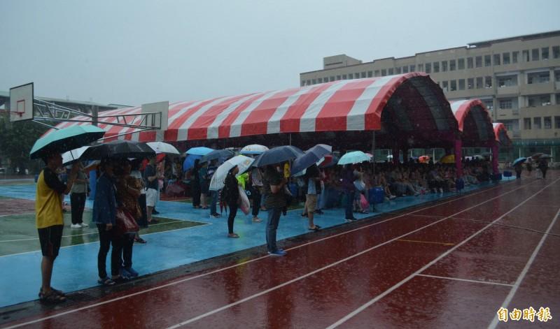 大里區成功國中至今沒有活動中心,今天克難搭棚架舉辦畢業典禮,家長撐傘參加,師生、家長全都「濕身」。(記者陳建志攝)