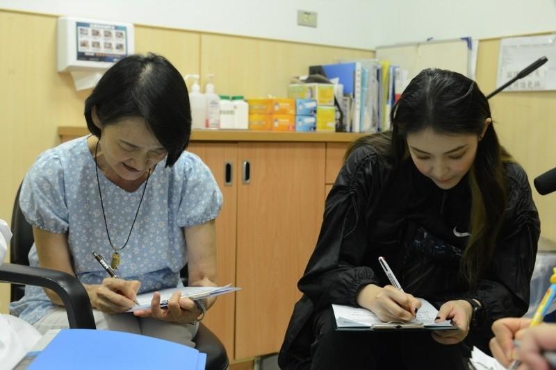 譚艾珍(左)與女兒歐陽靖(右)簽署預立醫療決定書。(台北慈濟醫院提供)