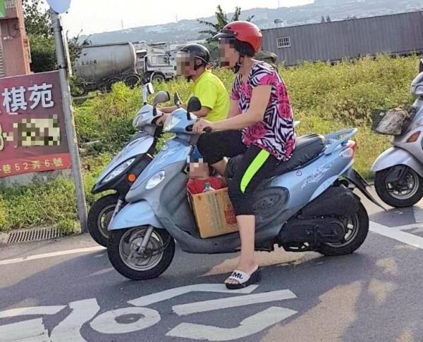 一位媽媽將小孩「裝箱」,放在機車腳踏板,引發往來用路人目光。(記者謝介裕翻攝)