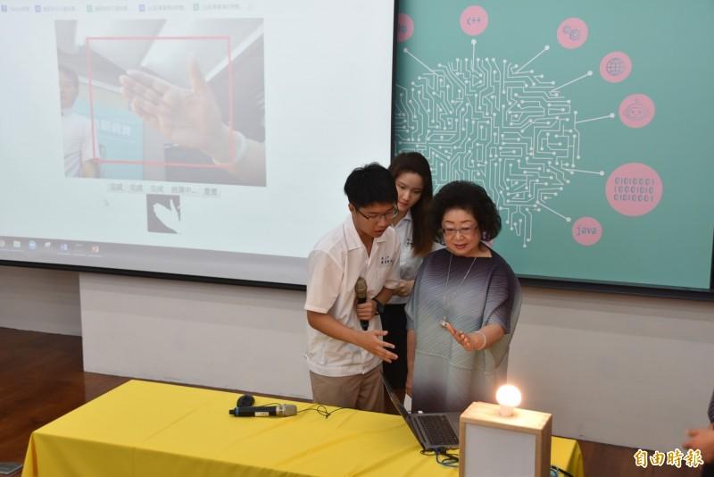 台南二中學生向教育部次長范巽綠(右)說明AI電腦系統,並教導進行手部動作剪刀、石頭、布的辨識,成功讓機器透過學習,完成任務。(記者吳柏軒攝)