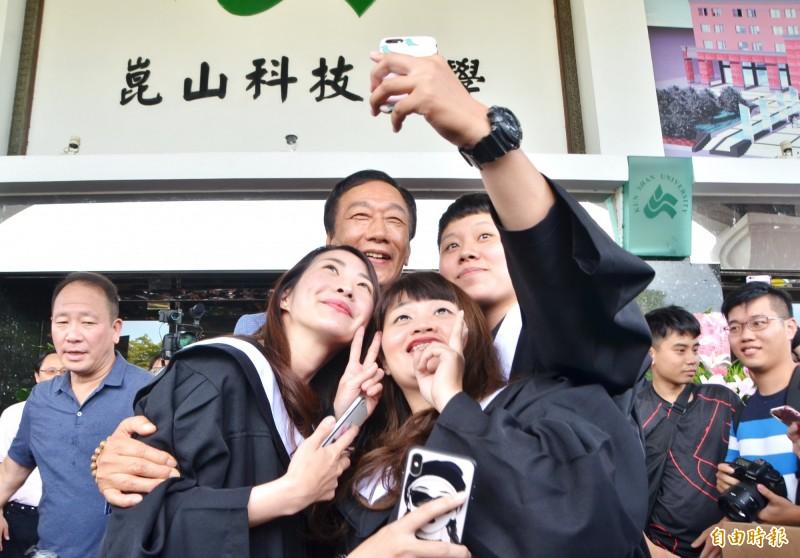 鴻海董事長郭台銘(後中)與畢業生玩自拍。(記者吳俊鋒攝)