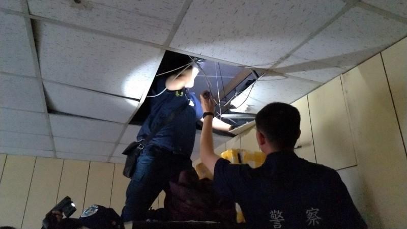 桃園市專勤隊人員檢查天花板有無藏匿非法外籍人士。(記者魏瑾筠翻攝)