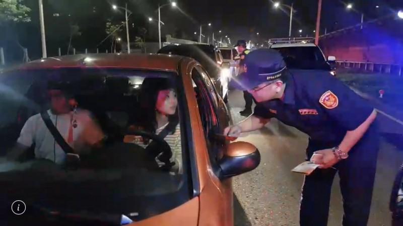 台中市交大大隊長林沐弘分送酒駕新法宣導單給駕駛提醒。(記者許國楨翻攝)