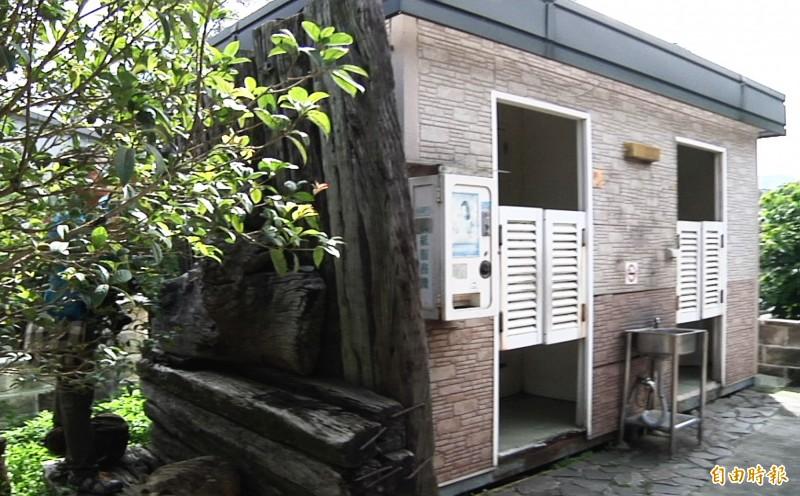 「傳承」前遭桂花樹遮蔽,加上公廁就位在創作後方,形同「屏風」。(記者彭健禮攝)