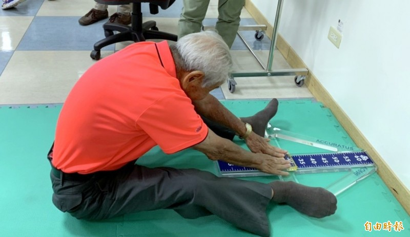 南投縣竹山秀傳醫院舉辦幸福階梯「救、九、久」活動,92歲高齡的阿公許清華展現筋骨柔軟的一面。(記者謝介裕攝)