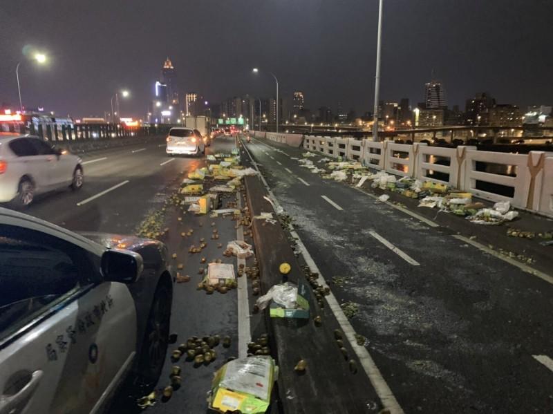 警方獲報查看,發現忠孝橋上散落數箱奇異果。(記者王宣晴翻攝)