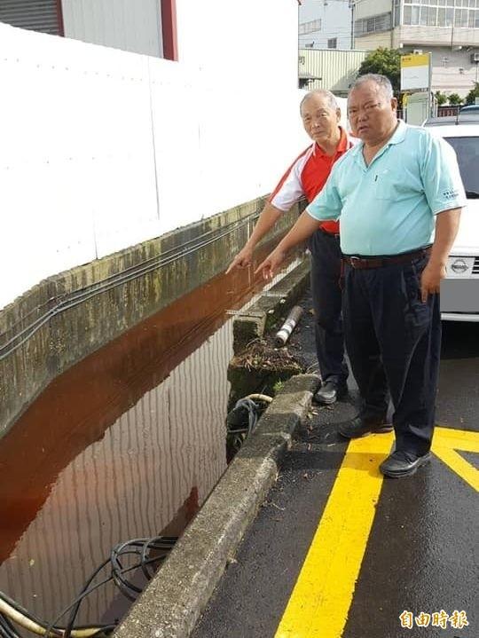 大里區國中路的排水溝昨天下午出現紅色廢水,市議員張滄沂(右)、夏田里長胡金鍊(左)通報環保局要求追出元兇開罰。(記者陳建志攝)