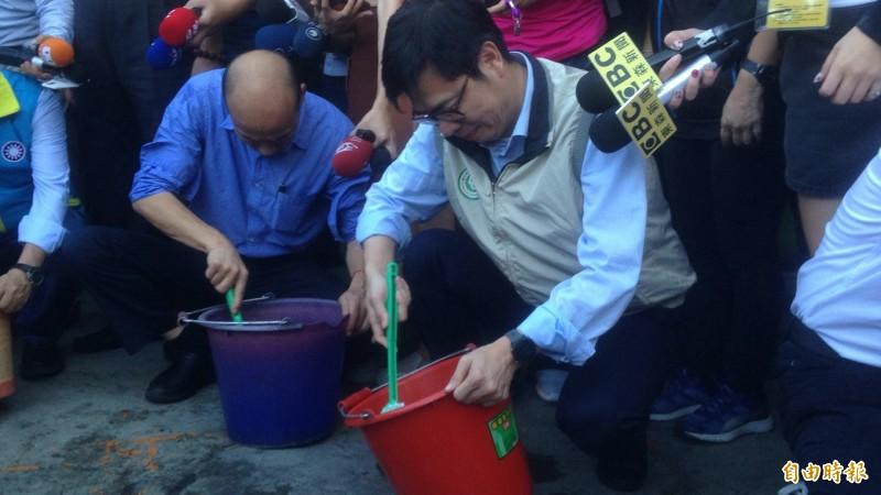 韓、陳於金獅湖市場傾倒積水。(記者黃旭磊攝)