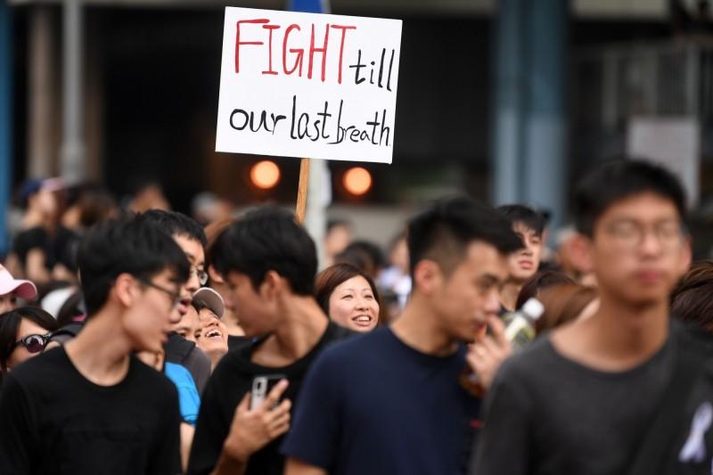 香港十六日反送中條例示威遊行中,示威者拿著「戰到最後一口氣」標語,表達堅持到底決心。(法新社)