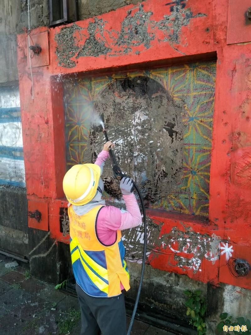 南市環保局清潔人員以高壓水柱除去女人頭像塗鴉圖。(記者王俊忠翻攝)