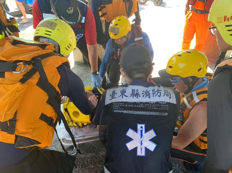 海巡人員及警消合力將昏迷的鄧姓女潛水客救上岸,並緊急送醫。(記者王秀亭翻攝)