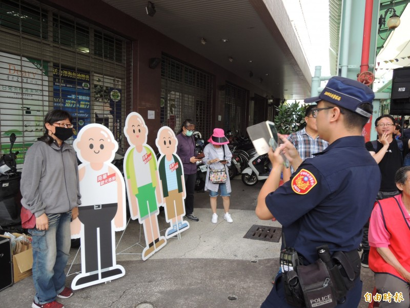 轄區員警發揮為民服務精神,協助民眾與光頭人形立牌拍照。(記者王榮祥攝)