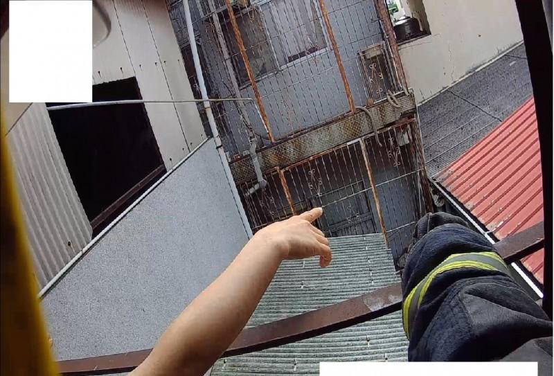 陳姓國中男學生爬鐵窗攀爬至1樓地面,但受困防火巷,經警消人員導引才脫困。(記者丁偉杰翻攝)