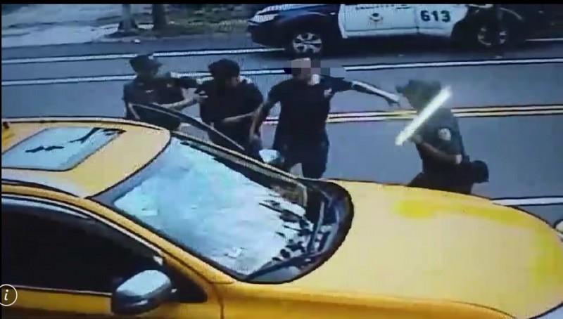宜蘭縣羅東鎮2名黑衣人(右2及左2),在警方面前追打林姓運將。(記者江志雄翻攝)