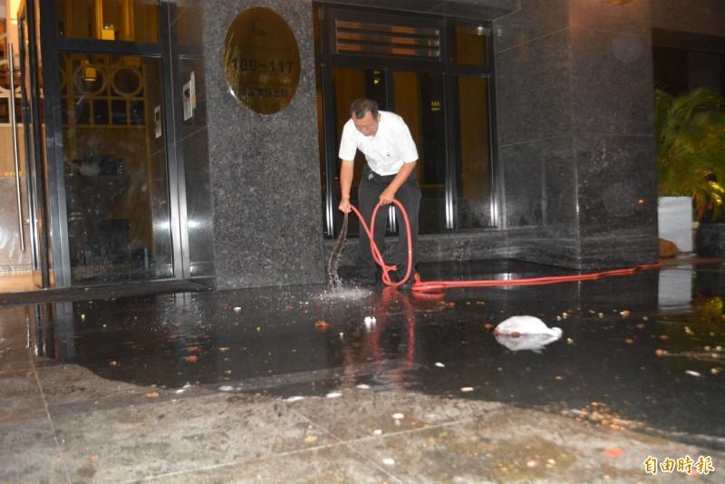 抗議民眾拿雞蛋丟擲洩憤,社區管理人員連夜清洗滿是蛋汁的地面。(記者陳建志攝)