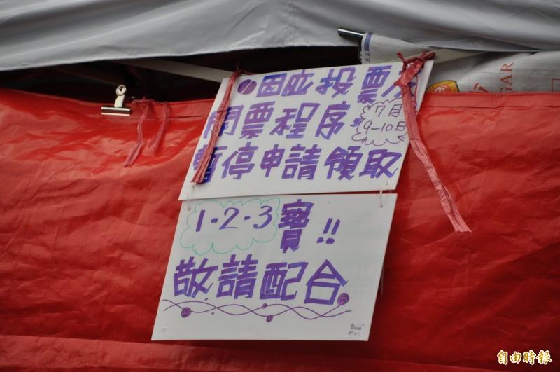 紙牌上寫明「9至10日暫停申請領取三寶」。(記者周敏鴻攝)