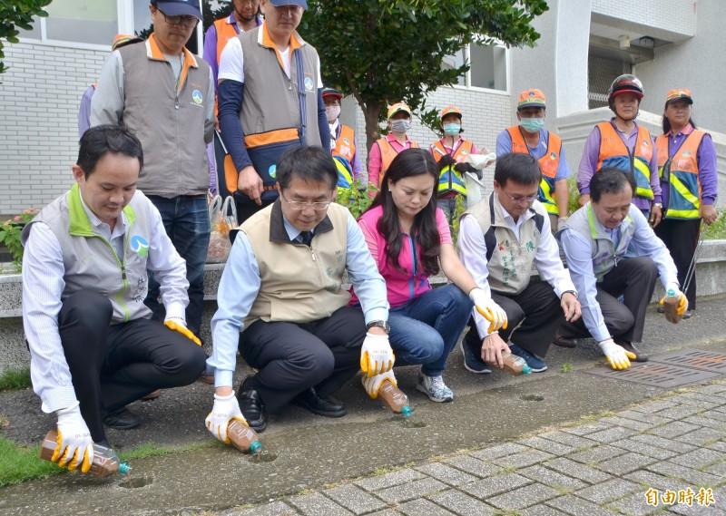 市長黃偉哲(左二)視察校園,並示範清除水溝孳生源的投藥工作。(記者吳俊鋒攝)