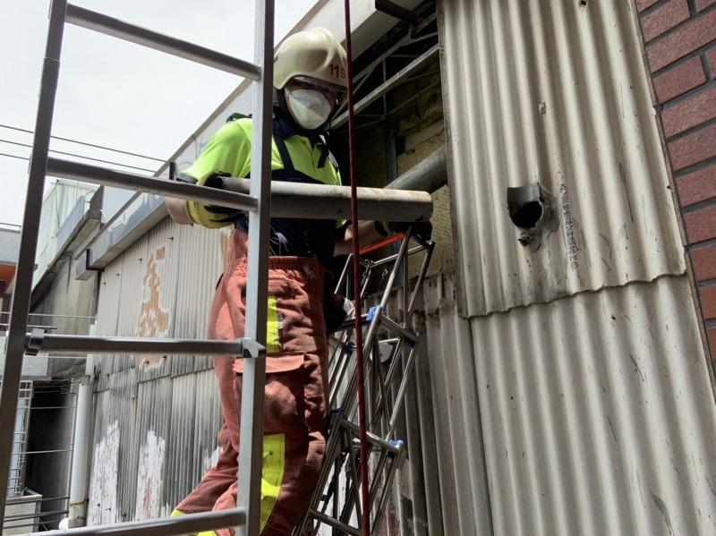 新竹市消防局光復分隊員架梯截斷排水管,救出「卡管」小貓咪。(記者洪美秀翻攝)