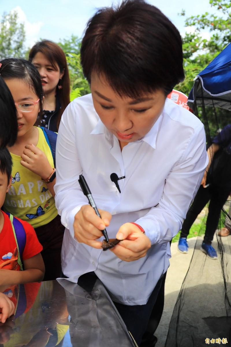 市長盧秀燕嘗試標放紫斑蝶。(記者蔡淑媛攝)