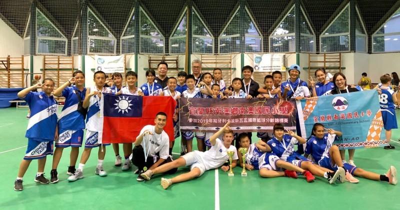 宜蘭縣南澳國小籃球隊赴匈牙利參賽,摘下1冠軍、1亞軍,球員合照時秀出國旗。(記者江志雄翻攝)