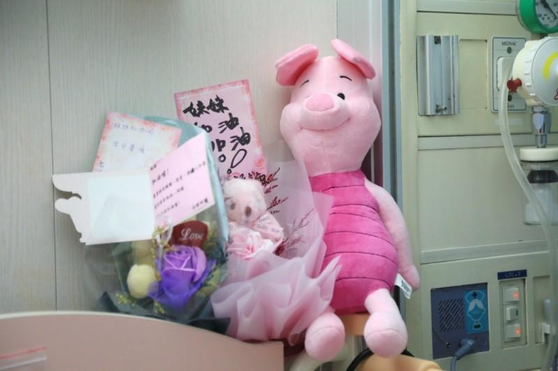 媽媽把善心民眾送的玩偶放在女童床前,為她加油打氣。(市府提供)