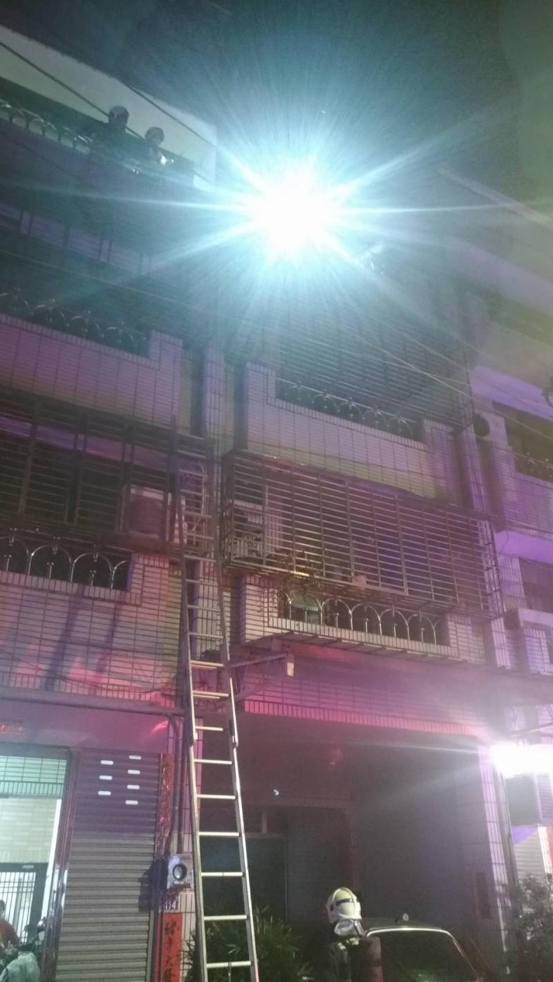 消防員架設梯子,將受困4樓的婦人救出。(記者張瑞楨翻攝)