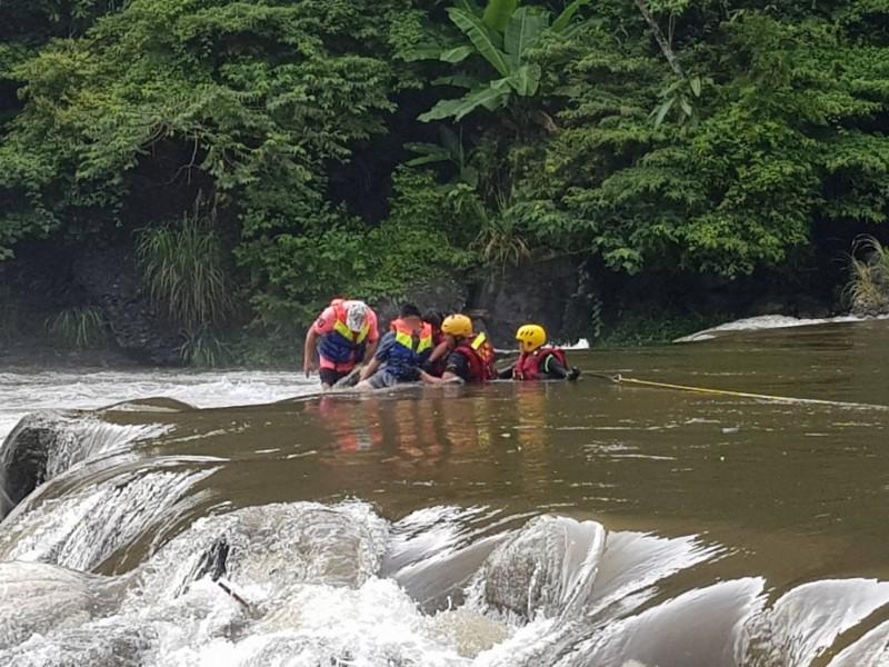 消防人員以繩索將受困溪中的民眾救上岸。(記者徐聖倫翻攝)
