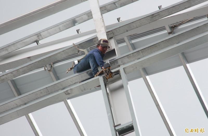工人穿著防墜設備,小心翼翼的在7樓高鋼骨上施工。(記者陳冠備攝)