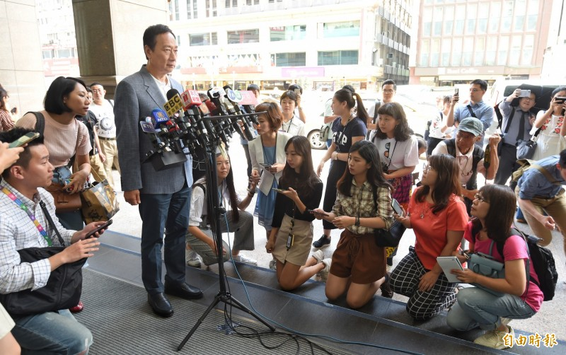 眾家媒體記者一擁而上,既要聽清楚郭台銘的訪問內容,又要顧及後方攝影機取景的需求,於是有多位記者同時以跪姿記錄採訪。(記者劉信德攝)