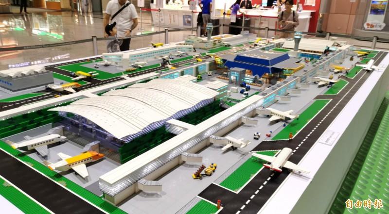 台灣唯一的「樂高認證大師」黃彥智耗時半年,,以15萬塊各式樂高積木打造18平方公尺的迷你樂高桃園機場,連第3航站(色拱型建築)現身其中。(記者姚介修攝)
