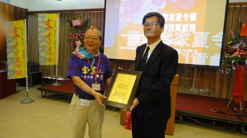 楊長鎮(右)頒奬給客家夏令營貢獻獎得主張義品(左)。(記者李容萍翻攝)